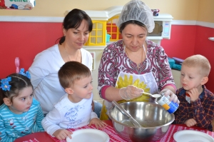 The cook shows children how to mix ingredients for cookie dough
